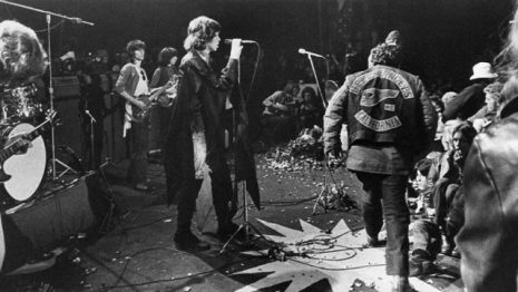 Mick Jagger sings at the Altamont Rock Festival at Livermore, Calif. on Saturday, December 6, 1969 while Hells Angels cross stage during melee to help fellow motorcyclists.