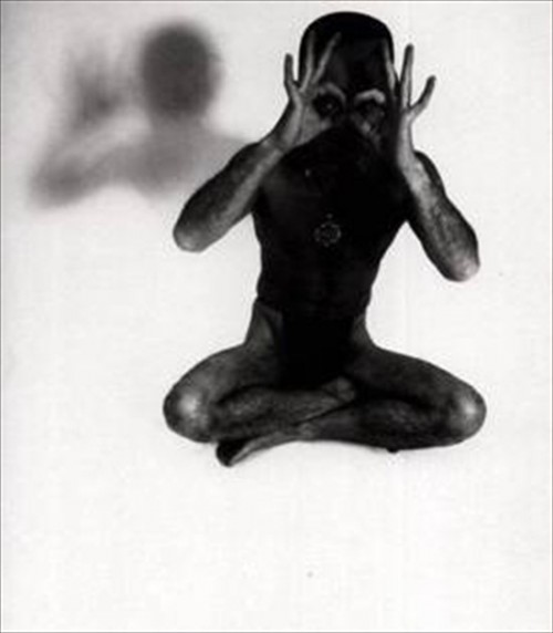Yukio-Mishima-semi-nude-and-seated-in-a-position-resembling-that-of-meditation