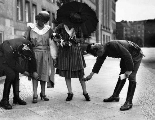 Original 1920s Berlin photo showing Police stopping and checking two young ladies to see if their dresses are not too short.