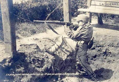 Српски војник, 12 година, нишани ка Аустро-угарима који се искрцавају.
