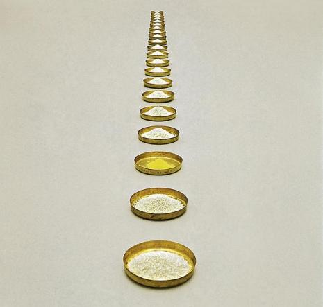 """Obroci od pirinča"", 1998. Tanjiri od mesinga, pirinač i polen lešnika (936 x 25 cm)."