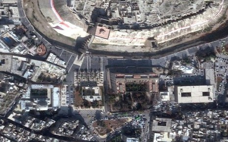 A satellite shot of the same area from July 14 2014 shows the destruction of the Khusriwiye Mosque (green arrow) and the Carlton Citadel Hotel (blue arrow). Image ©2014, DigitalGlobe, NextView License | Analysis AAAS.(www.telegraph.co.uk)